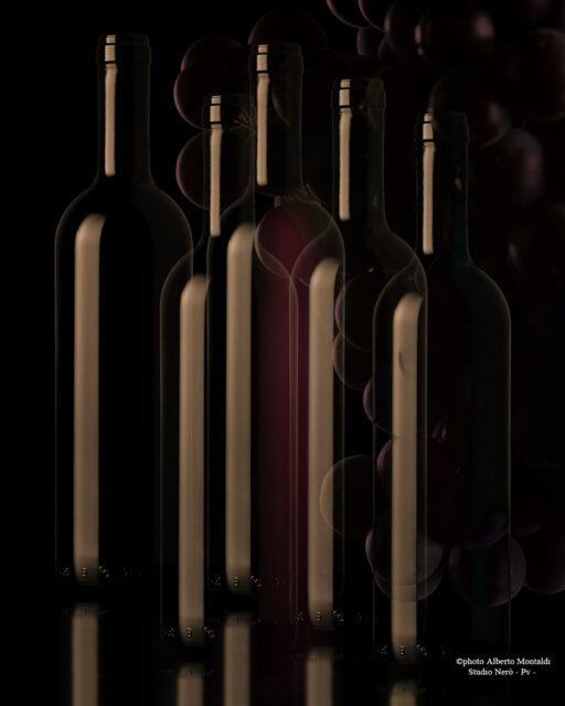 composizione bottiglie bordolesi con uva in trasparenza