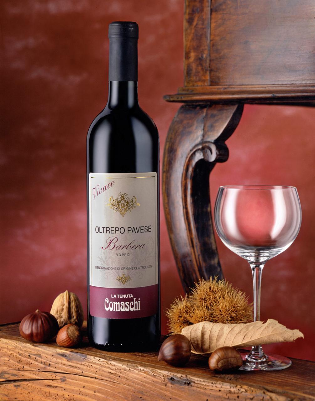 Foto del Vino Rosso Barbera Comaschi con scenografia: Bicchiere,Frutta Secca,Sfondo Rosso e Tavolinof