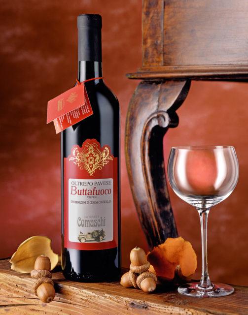 Foto del Vino Rosso Buttafuoco Comaschi con scenografia: Bicchiere,Ghiande,Fiori di Magnoglia,Sfondo Rosso e Tavolino