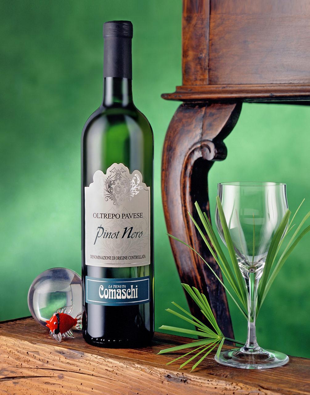 Foto del Vino Bianco Pinot Nero Comaschi con scenografia: Bicchiere,Sfera e Pesciolino di vetro,Foglie di Papiro,Sfondo Verde con Tavolino