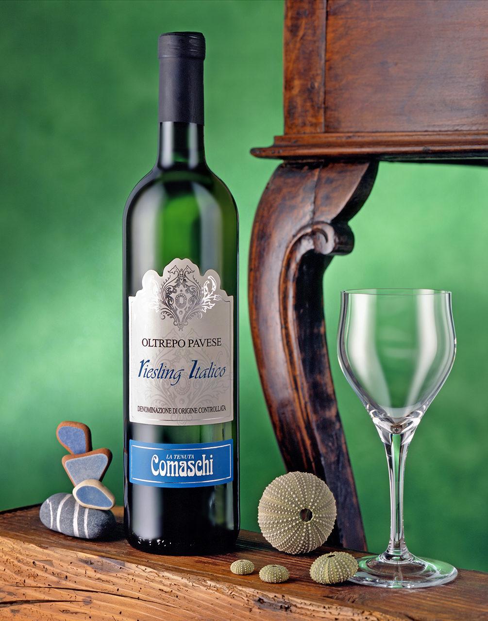 Foto del Vino Bianco Riesling Italico Comaschi con scenografia: Bicchiere,Ricci di Mare,Sassi Riviera Ligure,Sofndo Verde con Tavolino