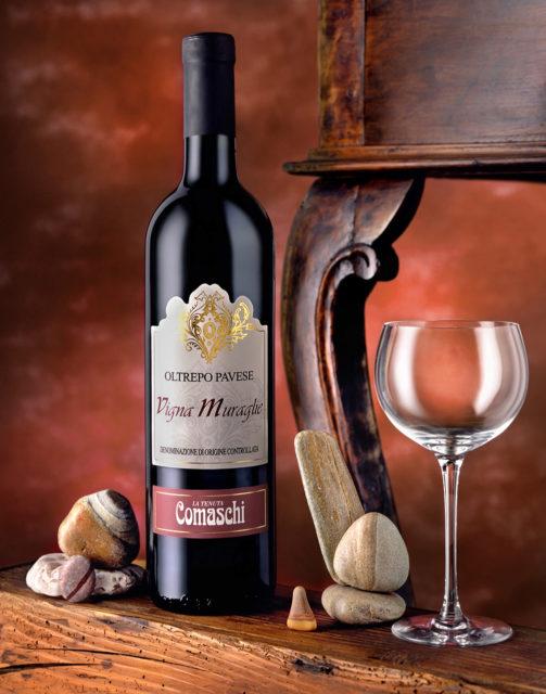 Foto del Vino Rosso Vigna Muraglie Comaschi con scenografia:Bicchiere,Sassi Costa Sarda,Sfondo Rosso anticarro e Tavolino.